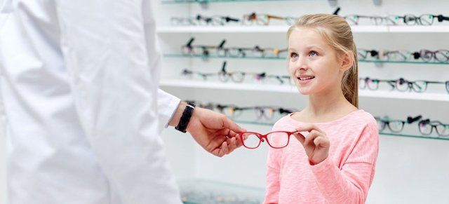 optician helping a child pick her glasses